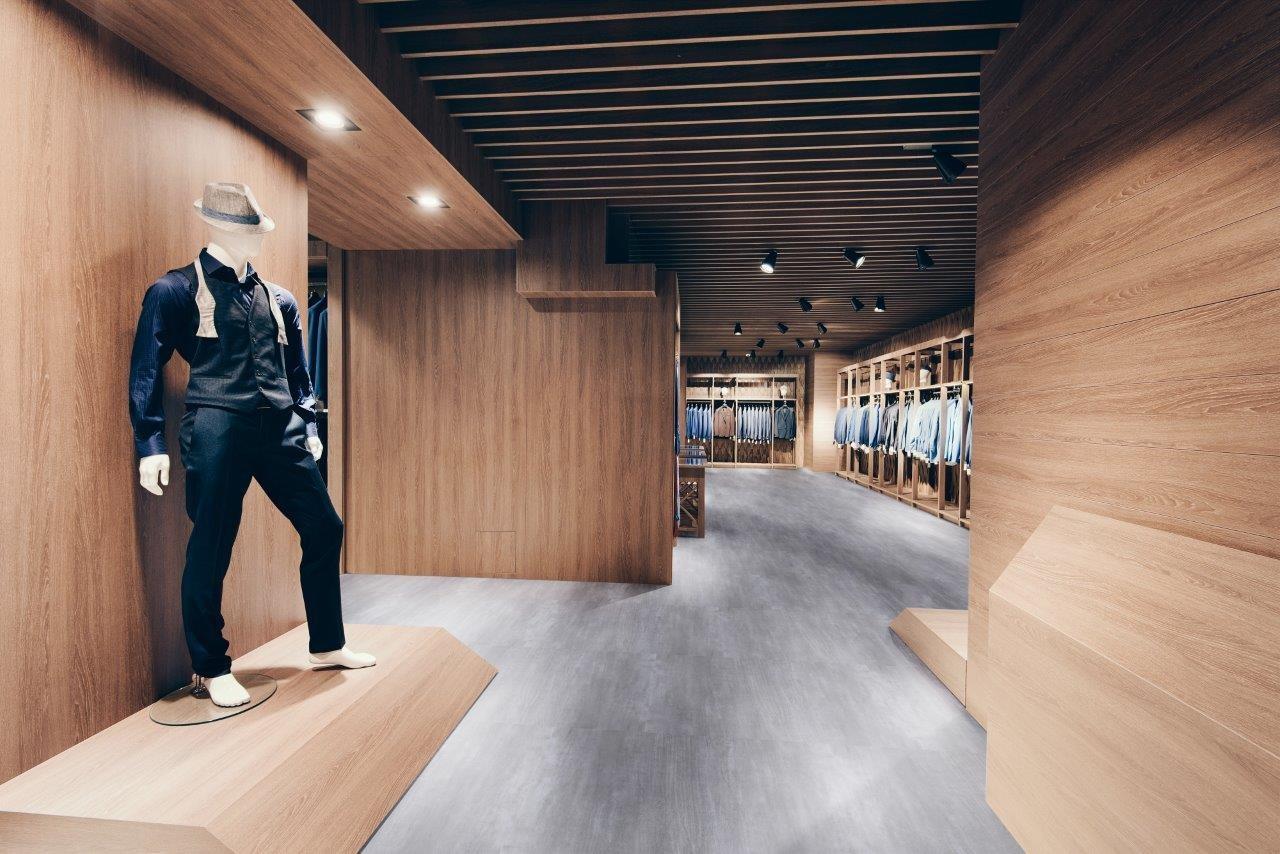 corredor com um manequim de preto, paredes de madeira e piso vinílico cinza