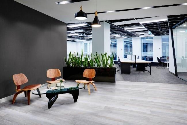 escritório com uma mesa de vidro na frente e uma parede com vinílico marrom ao lado