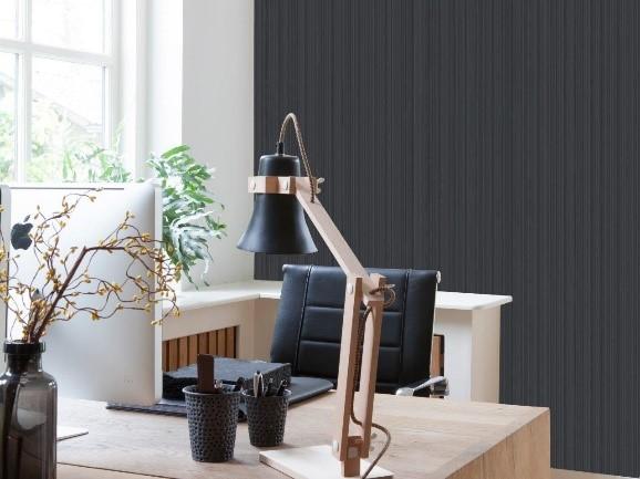 home office com uma mesa de madeira e uma cadeira preta e vinílico preto atras na parede