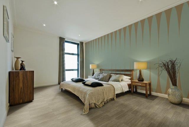 quarto moderno com cama de casal no centro, piso vinilico marrom claro e uma parede verde agua e detalhes em marrom