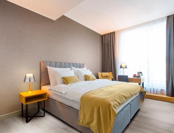 quarto com cama amarela e branca com vinílico marrom na parede atrás