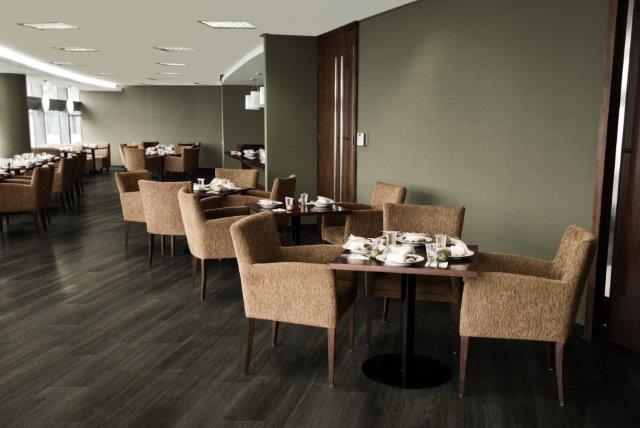 pequenas mesas de um café com poltronas marrom e piso vinilico marrom escuro no chão