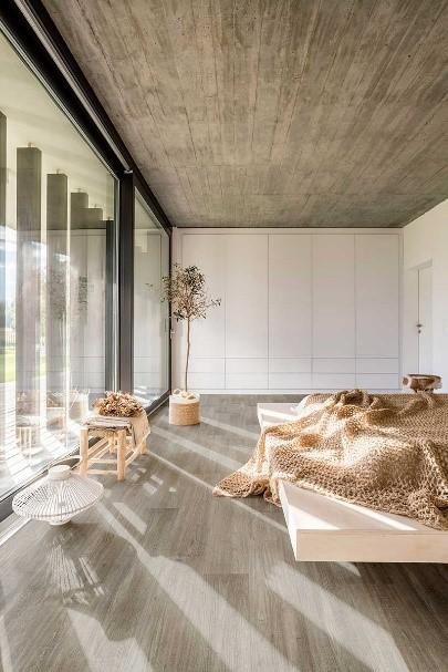 quarto de uma casa moderna com janela de vidro grande e uma cama moderna e piso vinilico marrom
