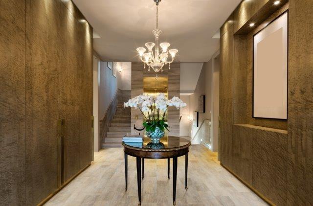 corredor com paredes marrom, uma mesa central com um vaso com flor no centro e piso vinilico marrom claro no chão
