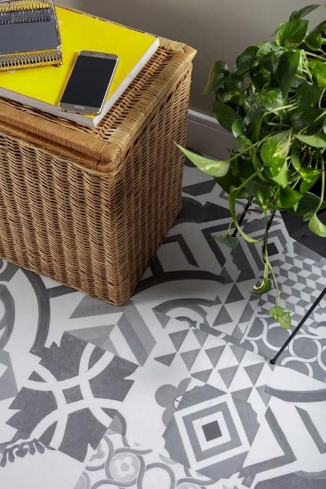 piso vinilico com formatos geometricos cinza e uma mesinha com planta em cima